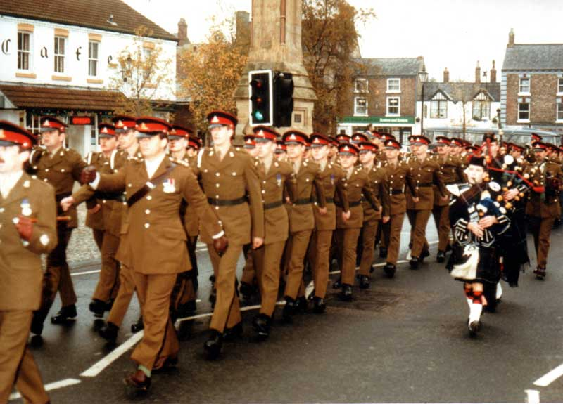 Pipe Major Mark Jamieson, Yorkshire based Scottish bagpipe player with 25/170 Battery Royal Artillery marching through Thirsk after receiving the freedom of the town